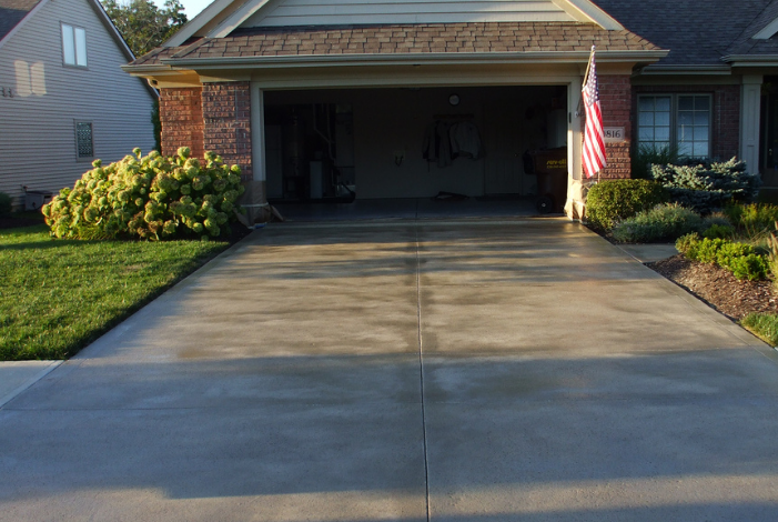 Picture of stained and died concrete driveway.